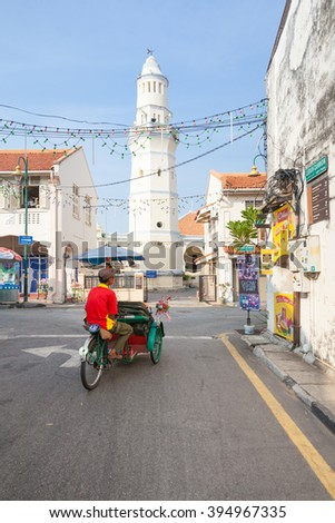 George Town,  Malaysia - March 21, 2016: Cycle rickshaw is riding down the street in front of the Lebuh Aceh Mosque. on March 21, 2016 in George Town, Penang, Malaysia.