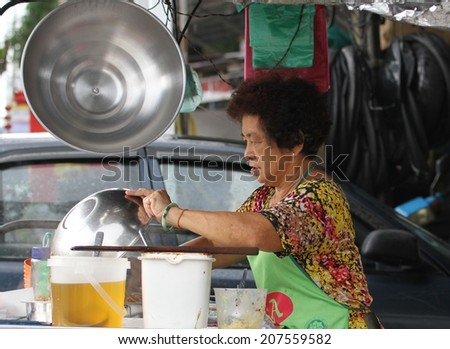 GEORGE TOWN, MALAYSIA - MAY 30: A local Malay woman cooking at a street stall in George Town, Malaysia on the 30th May, 2014.