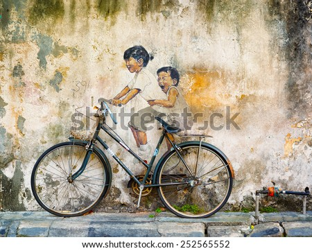 GEORGE TOWN, PENANG, MALAYSIA - CIRCA JUL 2014: Public art in Malaysia uses contrasting media of sculpture and painting for this mural of two girls riding a bicycle. - stock photo