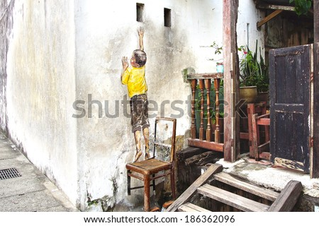 "GEORGETOWN, MALAYSIA - JANUARY 19, 2014: ""Reaching Up"" Mural. The painting was created by Ernest Zacharevic in conjunction with the 2012 George Town Festival.   - stock photo"