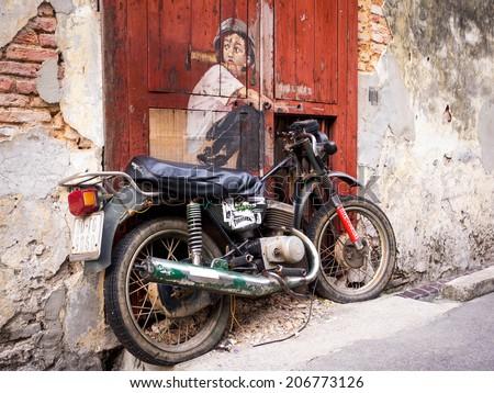 "Georgetown, Penang, Malaysia - April 23, 2014: ""Boy on a Bike"" street art mural by Lithuanian artist Ernest Zacharevic in George Town, Penang, Malaysia. - stock photo"