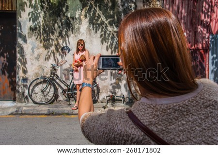 """Georgetown, Penang, Malaysia - February 19, 2015: Tourists are taking photos with """"Little Children on a Bicycle"""" art on wall by Lithuanian artist Ernest Zacharevic in George Town, Penang, Malaysia. - stock photo"""