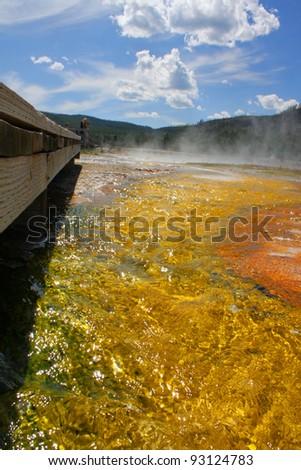 Geothermal pool next to a wooden walking bridge. - stock photo