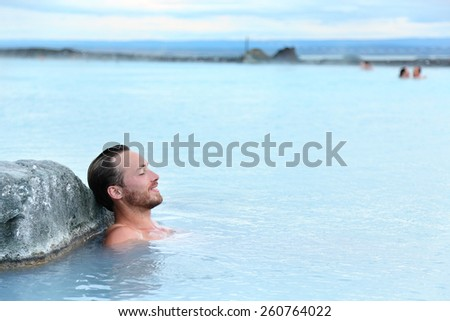 Geothermal spa. Man relaxing in hot spring pool on Iceland. Young man enjoying bathing relaxed in a blue water lagoon Icelandic tourist attraction. - stock photo