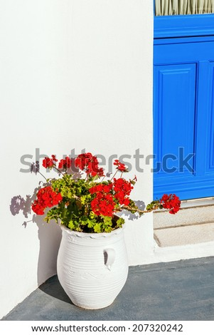 Geranium flower pot beside a blue door in Mykonos, Cyclades, Greece - stock photo