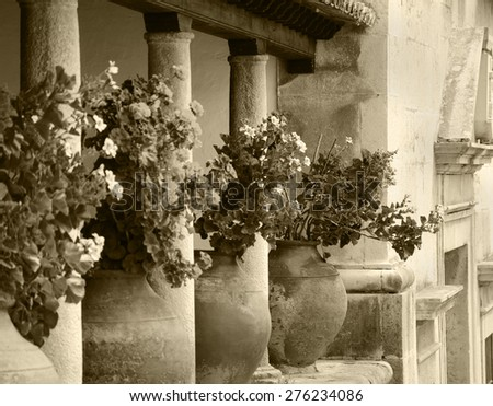 Geranium flowers in big ceramic pots between the columns at the terrace of old house. Obidos, Portugal. Selective focus on remote flowerpot. A game of light and shadow. Aged photo. Sepia.  - stock photo
