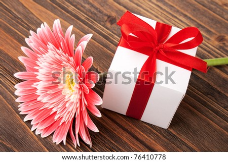 gerber flower and gift box on wood background