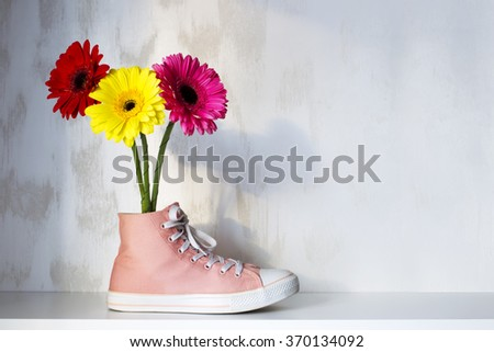 Gerbera flowers are in a vase made out of shoes on the shelf - stock photo