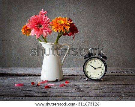 Gerbera flowers with vintage clock on wooden table over grunge background - stock photo