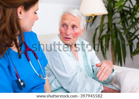 Geriatric doctor and elderly woman patient talking in the nursing home, spending time.