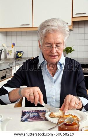 Geriatric nurse helping senior at breakfast - stock photo