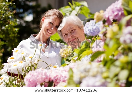 geriatric nurse with senior woman in the garden - stock photo