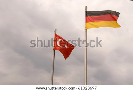German and Turkish flags on the background of dark cloudy sky.