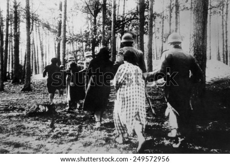 German atrocities in Poland ca. 1941. Polish women led by soldiers through woods to their execution during World War 2. - stock photo