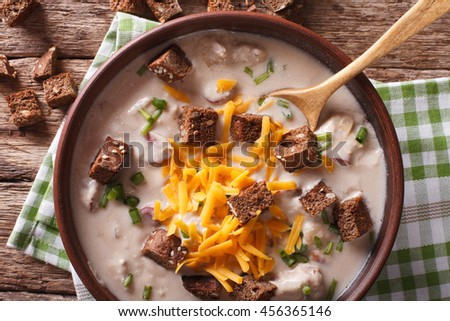German beer soup with cheese and bacon close up in a bowl on the table. Horizontal view from above - stock photo