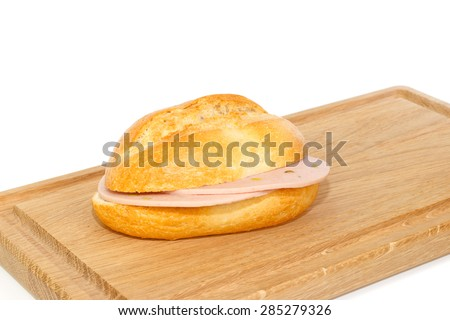 German bread roll with mortadella on a wooden breakfast tray against white background - stock photo