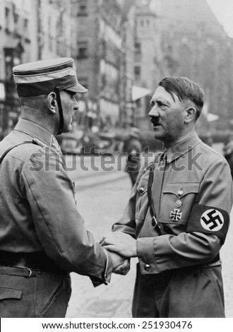 German Chancellor, Adolf Hitler, shaking hands with a Brownshirt at Nazi Party Day. Nuremberg, 1937. ) - stock photo