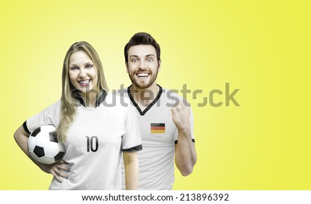 German couple soccer fan holding a soccer ball on yellow background