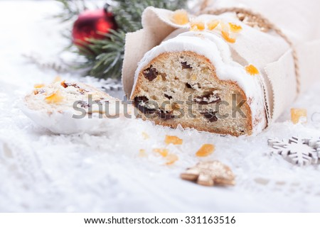 German dresdner stollen cake with raisins and candied oranges on a white background with false snow - stock photo