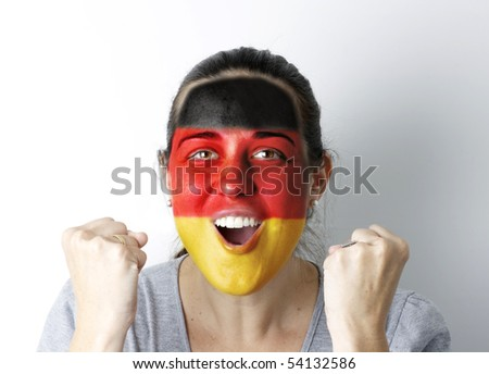 German fan screaming GOAL with hands up and painted flag on her face.