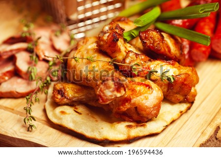 German food concept. Set of fried meat and small meat sausages served with scallion and dried herbs on wooden cutting board. Close up - stock photo
