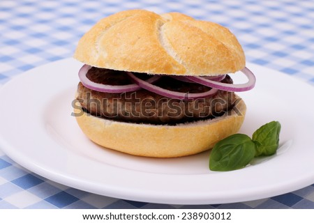 German Hamburger on plate, white blue checkered tablecloths, close up - stock photo