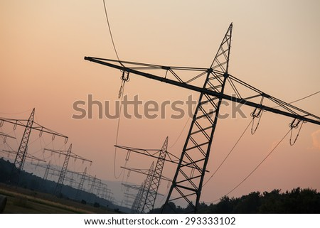 german high voltage pylons in an evenign sundown - stock photo