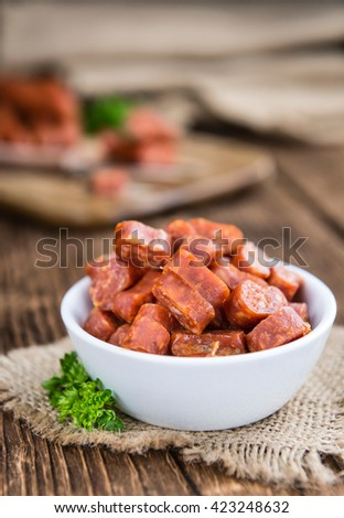 German Mettwurst (Chilli flavoured) as close-up shot (selective focus) on wooden background - stock photo