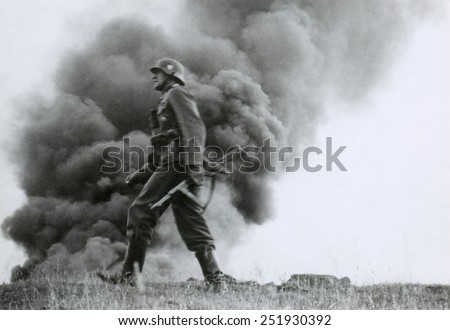 German officer of assault troops during the Nazi invasion of the Soviet Union, (Russia) In the Summer of 1941, the soldier strides against a background of burning buildings, during World War 2. - stock photo