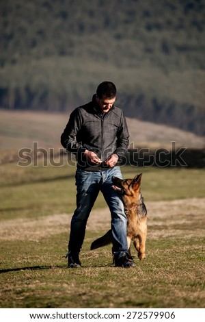 german shepherd dog and his master training in the field - stock photo
