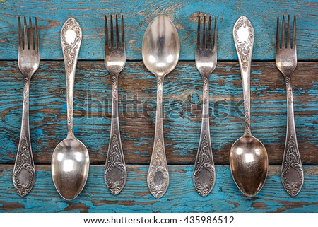 German silver spoon and fork on a wooden background. Kitchen utensils.