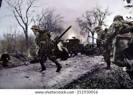 German soldiers of the 2nd SS Panzer Division run across a road blocked by destroyed U.S. vehicles. Dec. 16-22, 1944. Battle of the Bulge, Belgium. B&W Photo with oil color. - stock photo