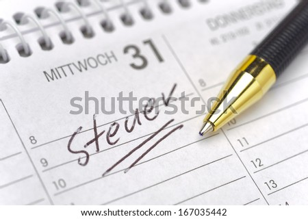 german tax day marked on calendar- tax translated  in german: Steuer - stock photo