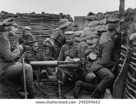 German WW1 soldiers with machine gun 40 meters from the British trenches. 1916. A soldier with the metal helmet is ready to throw a hand grenade. - stock photo