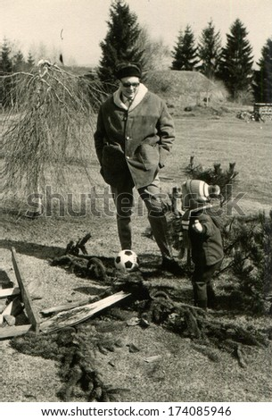 GERMANY -  1986: An antique photo shows man in a fur coat and hat with earflaps walks in the park with a small boy,