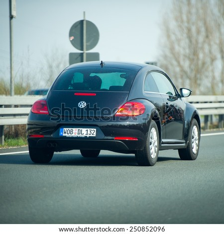 GERMANY - APRIL 3: VW Beetle on German Autobahn on April 3, 2014 in Germany. Volkswagen is a German automobile manufacturer and the biggest German automaker. - stock photo