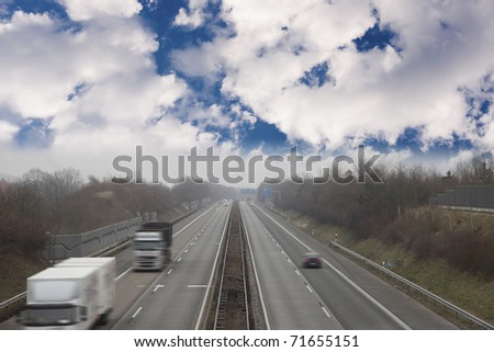 """germany """" autobahn """" the german highway..image taken on a cloudy day with some fog. image with motion blur . - stock photo"""