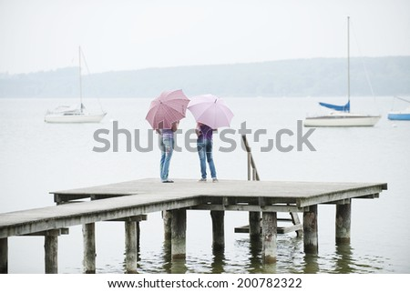 Germany, Bavaria, Ammersee two Women standing on jetty holding umbrellas rear view