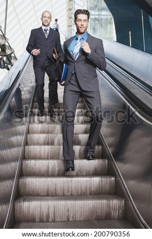 Germany, Bavaria, Munich business people on escalator business man running downstairs - stock photo