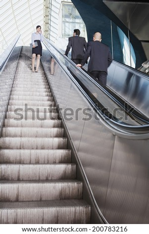 Germany, Bavaria, Munich business people on escalator business woman using mobile phone - stock photo