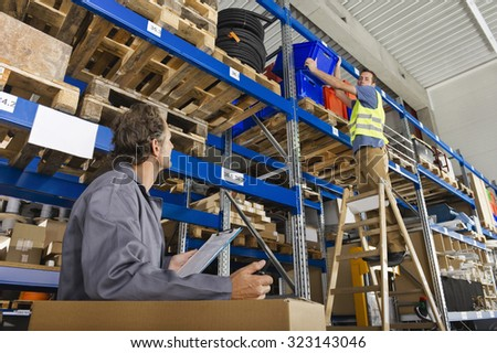 Germany,Bavaria,Munich,Manual workers working in warehouse - stock photo
