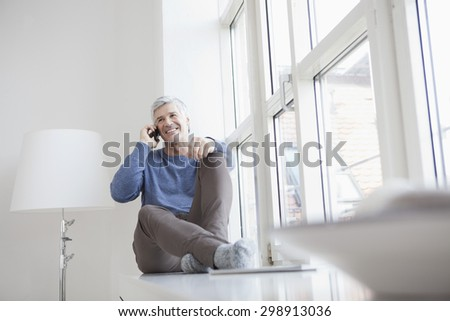 Germany, Bavaria, Munich, Mature sitting at window and talking on mobile phone, smiling