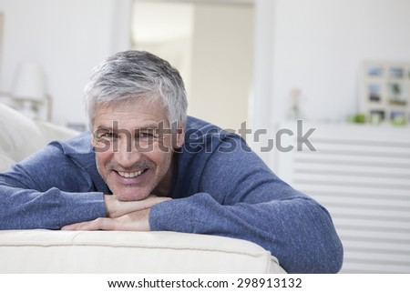 Germany, Bavaria, Munich, Portrait of mature man relaxing on couch, smiling