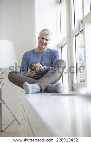 Germany, Bavaria, Munich, Portrait of mature man sitting at window, smiling