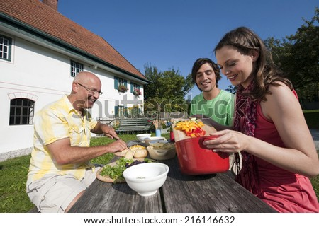 Germany, Bavaria, Two men and woman at table in garden preparing food