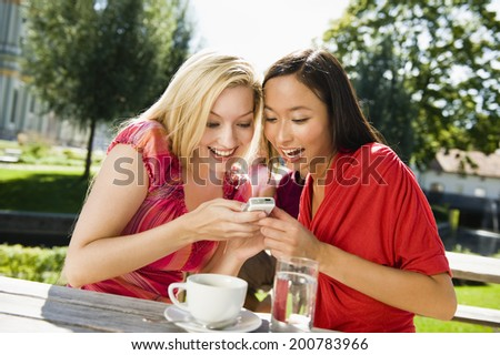 Germany, Bavaria, Upper Bavaria, two young women in beer garden looking amused at mobile phone