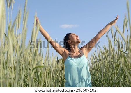 Germany, Brandenburg, young happy woman in grain field