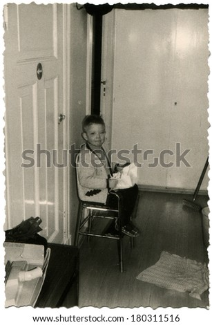 GERMANY - CIRCA 1975: An antique photo of little boy in a knitted jacket sitting on a metal chair outside the front door