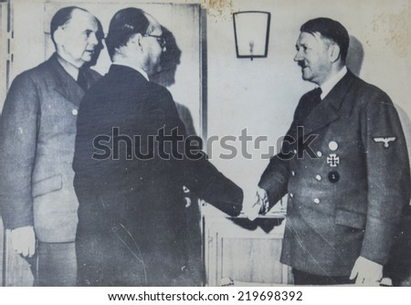GERMANY - CIRCA 1940s: Adolf Hitler shakes hands with one of the man during an official meeting. Antique photograph.  - stock photo