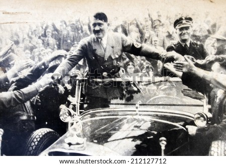 GERMANY - CIRCA 1940s: Adolf Hitler stands in a convertible and shaking hands with his fans,  Reproduction of antique photo. - stock photo